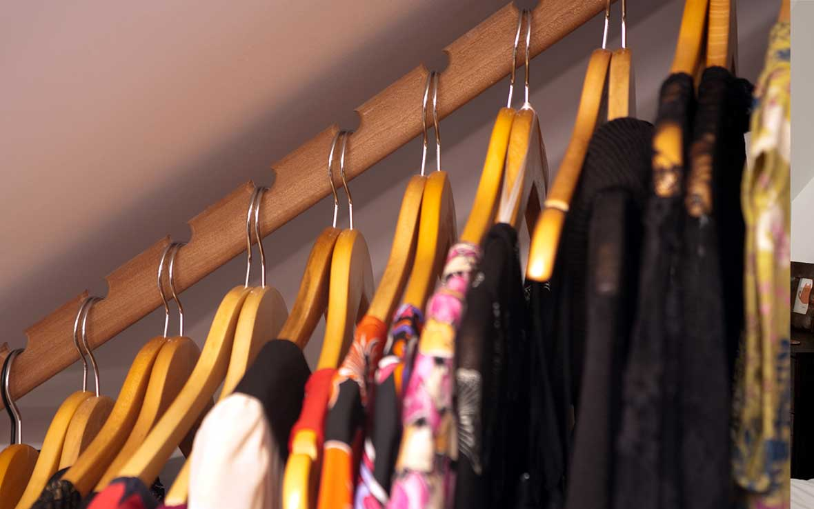 Bespoke clothes rail within walk-in wardrobe provides maximum storage