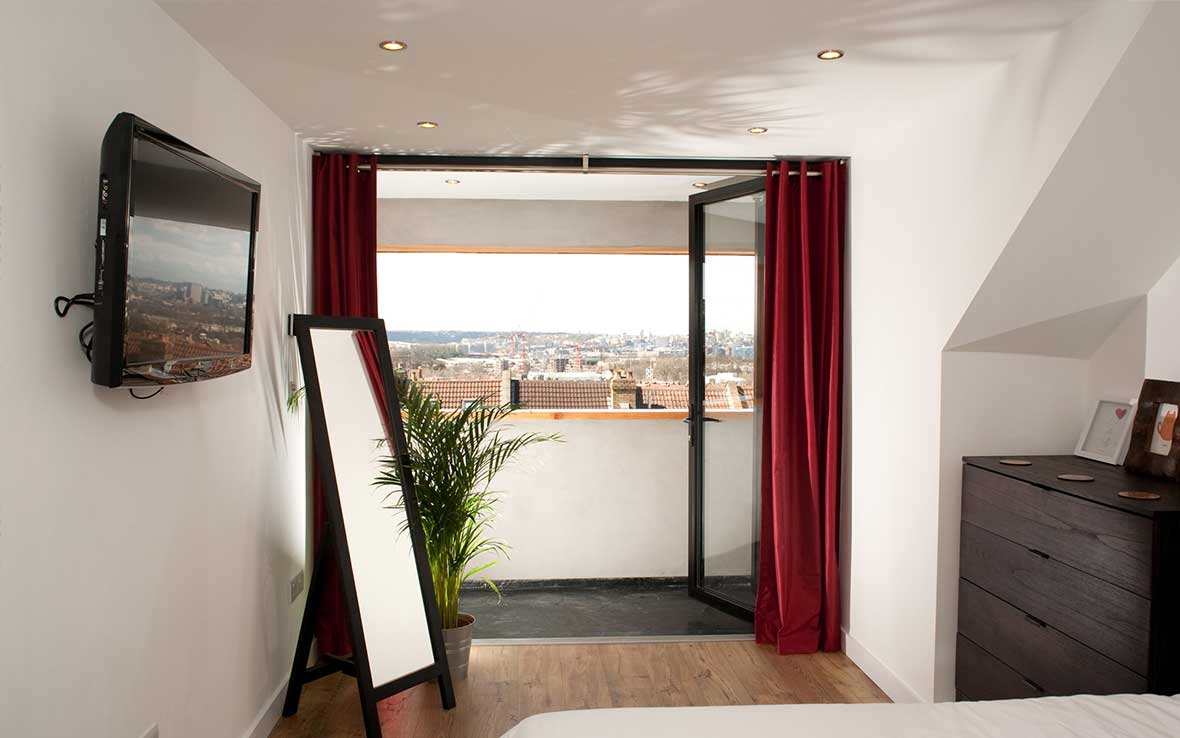Colour-coded bifold doors open onto balcony with panoramic view across Bristol