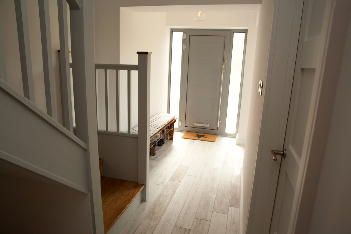 Hallway - high-quality AluTherm front door and screen, wood-effect white floor tiles