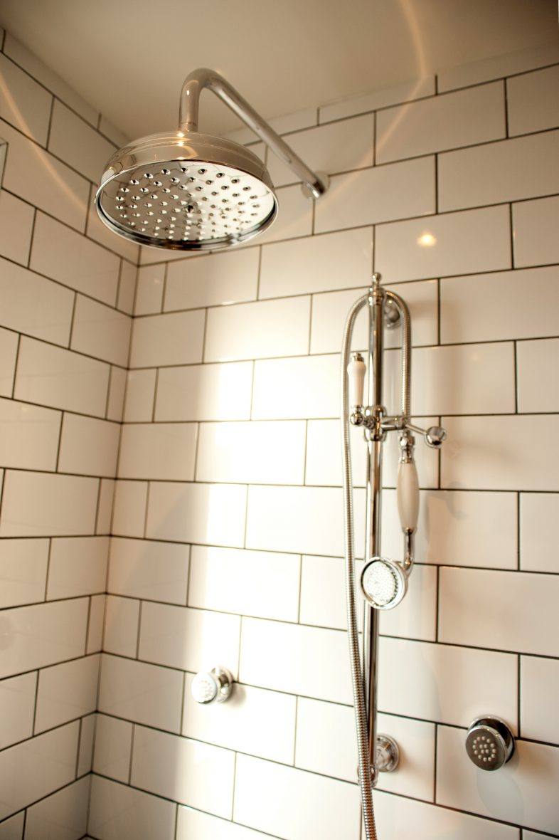 Shower enclosure incorporates body jets and rainfall shower head.